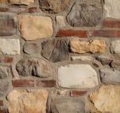 Lantlig textur för stenvägg Väggen göras av röda tegelstenar, cement och naturliga stenar Arkivfoto