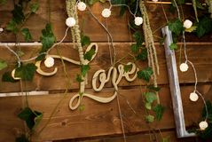 Lantlig träbröllopbackgdrop för att gifta sig Inskrift för förälskelsebokstäver dekorativa lampor Arkivbilder
