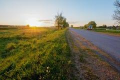 Lantlig väg i byn bredvid fältet på solnedgången Arkivfoton