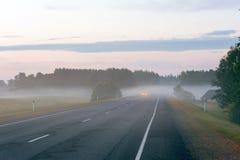 Lantlig väg med billyktor av bilen som visas till och med dimman Arkivbilder