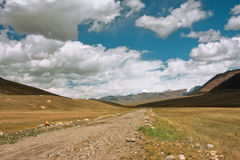 Lantlig väg mellan bergen av centrala Asien med stora moln i himlen för ett ögonblick för en åskväder Arkivfoton