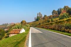 Lantlig väg och höstliga kullar i Piedmont, Italien Royaltyfria Bilder