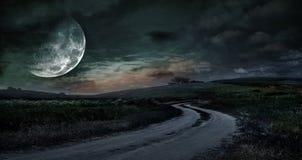 Lantlig väg till och med ängen på natten mot bakgrunden av Royaltyfria Foton