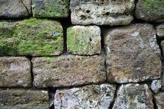 Lantlig vägg av naturliga stenar som en bakgrund Arkivfoto