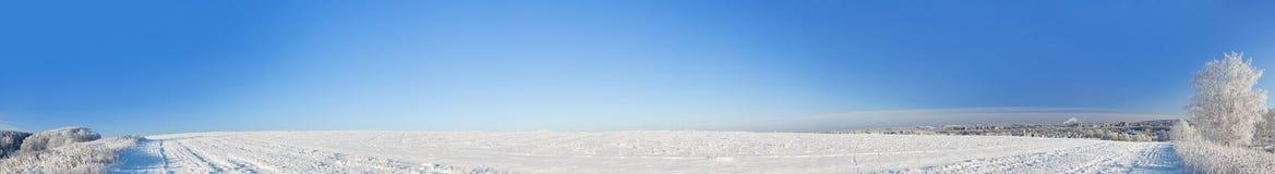 Lantlig vinterlandskappanorama med ett fält, snö, skog, stad fotografering för bildbyråer