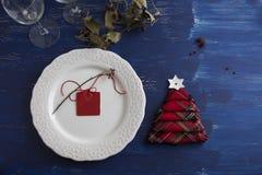 Lantlig vit platta för julmatställe och röda askar för servett i th Royaltyfri Fotografi