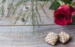 Lantlig wood bakgrund med den röda ros- och för choklad två godisen som förläggas på en sida Royaltyfria Foton