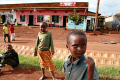 Lantliga afrikanska barn sitter tillbaka i bygatan Royaltyfri Foto