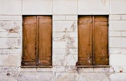 Lantliga gamla grungy och red ut bruna trästängda fönster stänger med fönsterluckor med skalningsmålarfärg på en vit sprucken väg Arkivfoto