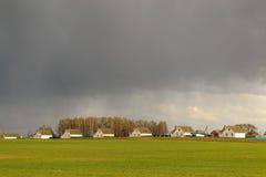 Lantliga hus i ett fält mot en dramatisk himmelbakgrund Arkivfoton