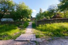 Lantliga hus på ett grönt gräs mattar i skuggan av fruktträd Fotografering för Bildbyråer