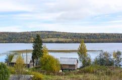 Lantliga hus på lakeside i taiga Arkivfoto