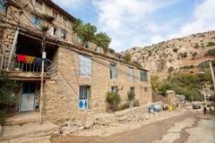Lantliga hus på lutningarna av ett brant berg av den kurdish byn Royaltyfri Bild