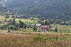 Lantliga hus på lutningen av forested berg Royaltyfria Foton