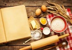 Lantliga ingredienser för kökbakningkaka och den tomma kocken bokar Royaltyfri Bild