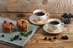 Lantliga muffin med den svarta vinbäret och två kopp kaffe Fotografering för Bildbyråer
