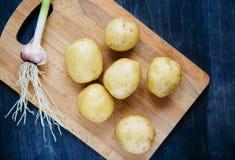 Lantliga potatisar och vitlök Arkivfoto
