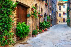 Lantliga tegelstenhus dekorerade med färgrika blommor, Pienza, Tuscany, Italien Arkivbild