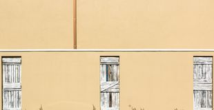 3 lantliga trästängda dörrar mot en Tan Background royaltyfria bilder