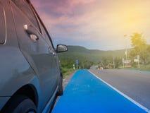 Lantligt berglandskap med kullar, berg, väg, blå sommarhimmel med moln och sol och bil som parkeras på vägrenen under a Royaltyfri Fotografi