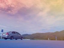Lantligt berglandskap med kullar, berg, väg, blå sommarhimmel med moln och sol och bil som parkeras på vägrenen under a Royaltyfria Foton