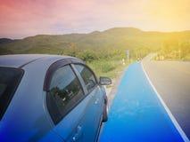 Lantligt berglandskap med kullar, berg, väg, blå sommarhimmel med moln och sol och bil som parkeras på vägrenen under a Royaltyfri Foto
