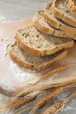Lantligt bröd och vete på en grå wood tabell för gammal tappning Arkivbild