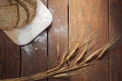 Lantligt bröd och vete på en wood tabell för gammal tappning Royaltyfri Foto