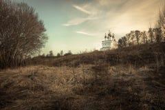 Lantligt bygdlandskaplandskap med kyrkan på kullen och solnedgånghimmel i vårsäsong royaltyfria bilder