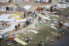 Lantligt folk som tvättar kläder i floden och som landar den på stranden Arkivfoto