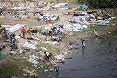 Lantligt folk som tvättar kläder i floden och som landar den på stranden, skott i Indien Rajasthan i 2011 Arkivbilder