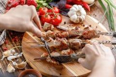 lantligt Händer klippte ett saftigt grisköttkött med en kniv Aptitretande kebaber och nya grönsaker på en träbakgrund 1 livstid f Royaltyfri Fotografi