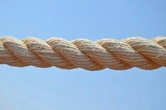 Lantligt havsrep som hänger på bakgrund för blå himmel, beige bomullstråd för att torka klädernärbild royaltyfri foto