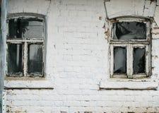 lantligt hus för tegelstenvägg med två lilla gamla skrangliga Windows Arkivfoto
