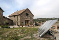 Lantligt hus med solpanelen Arkivbild