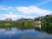 Lantligt hus på en sjö i skogen Royaltyfria Foton