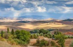 Lantligt landskap av Tuscany, Italien Fälten, kullarna och skogjordbruket Arkivbild