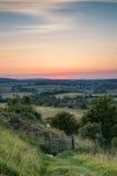 Lantligt landskap för engelsk bygd i sommarsolnedgångljus Royaltyfri Foto