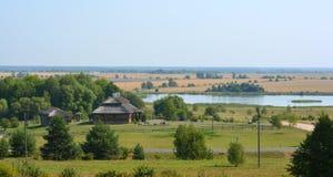 Lantligt landskap för sommar med den gamla stugan och sjön i Vitryssland royaltyfri bild