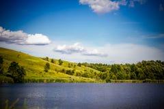 Lantligt landskap för sommar med sjön, Rollinget Hills, träden och bet Arkivfoton