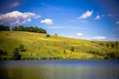 Lantligt landskap för sommar med sjön, Rollinget Hills, träden och bet Royaltyfria Bilder
