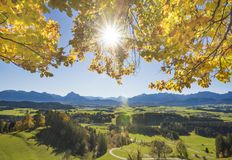 Lantligt landskap i Bayern med fjällängberg och solstrålar bak bokträdträd i höst fotografering för bildbyråer