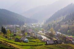 Lantligt landskap med byhus och berg Arkivbilder
