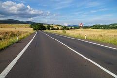 Lantligt landskap med den tomma vägen och den högra krökningen för trafiktecken framåt Arkivfoton