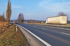 Lantligt landskap med en asfalthuvudväg Arkivbild