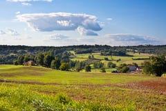 Lantligt landskap med en lantgård och en fileld Royaltyfri Foto