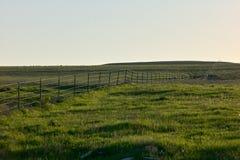 Lantligt landskap med ett staket på en grön kulle royaltyfri foto