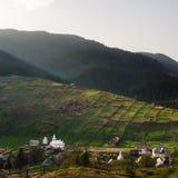 Lantligt landskap med hus och berg. Hus Arkivfoto
