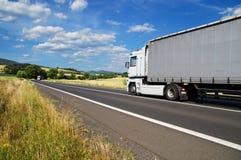 Lantligt landskap med vägen och att rida en vit lastbil, silverlastbil i avståndet Arkivfoton