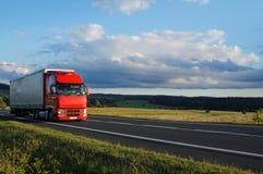 Lantligt landskap med vägen och den röda lastbilen för flyttning Arkivfoto